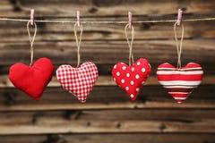 Liefdeharten die op kabel op de bruine houten achtergrond hangen Stock Foto