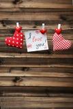 Liefdeharten die op kabel op de bruine houten achtergrond hangen Royalty-vrije Stock Foto