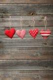Liefdeharten die op kabel op de grijze houten achtergrond hangen Royalty-vrije Stock Fotografie