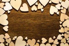 Liefdekader met lichte harten rond en donkere houten achtergrond i Stock Afbeelding
