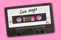 Liefdeliederen op uitstekende audiocassetteband worden geschreven, roze achtergrond die stock fotografie