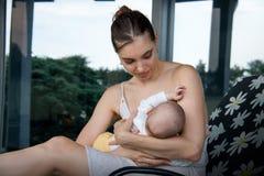 Liefdemoeder die weinig zoon verzorgen en in kleding op de ligstoel van het bloemgeklets voor groot grijs huisvenster zitten stock afbeelding