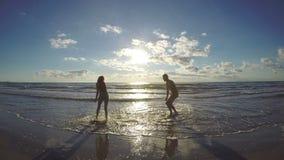 In liefdepaar die op strand naar het overzees lopen stock videobeelden