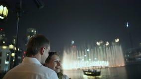 Liefdepaar die van elkaar op de achtergrond van fonteinen 2 genieten van de nachtstad stock footage