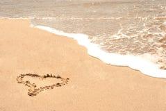 Liefdeteken op het strand stock foto's