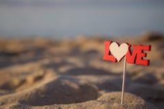 Liefdeteken in zand op strand stock afbeelding