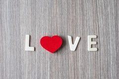 LIEFDEwoord die van houten alfabetbrieven met vrouwenhand rode hartvorm op lijstachtergrond houden Romaans, Romantisch en Valenti royalty-vrije stock afbeelding