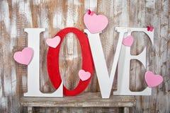 Liefdewoord met harten op houten plankenachtergrond Stock Afbeeldingen