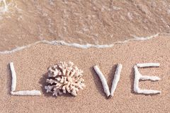 Liefdewoord van koralen op een tropisch strand wordt geschreven dat Stock Afbeeldingen