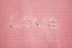 Liefdewoord van lovertjes, flikkering en confettien op roze achtergrond wordt gemaakt die stock foto's