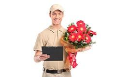 Lieferbote, der einen schönen Blumenstrauß anhält lizenzfreie stockbilder