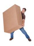 Lieferbote, der schweren Kasten trägt Lizenzfreies Stockfoto