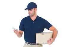 Lieferer, der Handy beim Halten des Pakets verwendet Stockfotografie