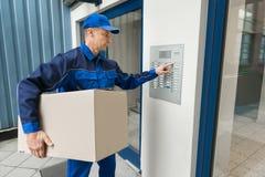 Lieferer, der Knopf der Wechselsprechanlage bedrängt, um Gebäude zu betreten lizenzfreie stockbilder