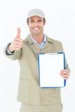 Lieferer, der oben Daumen beim Zeigen des Klemmbrettes gestikuliert Lizenzfreie Stockfotografie