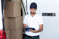 Liefererschreiben auf Klemmbrett bei der Stellung nahe bei seinem Packwagen Stockfoto