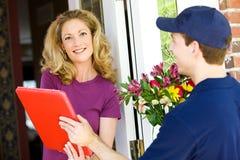 Lieferung: Hauseigentümer nimmt Blumenlieferung an Stockfoto