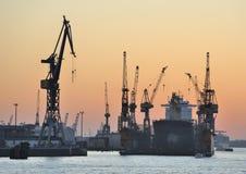 Lieferung im Dry-dock und Kräne am Sonnenuntergang Stockbilder