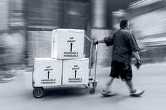 Lieferung mit Transportwagen eigenhändig in der einfarbigen blauen Tonalität Stockfotografie