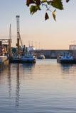 Lieferungen mit Reflexion im Hafen am Sonnenaufgang stockbilder