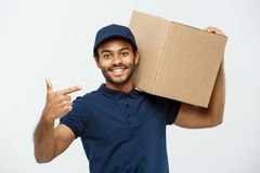 Lieferungs-Konzept - Porträt des glücklichen Afroamerikanerlieferers, der Hand zeigt, um ein Kastenpaket darzustellen ein getrenn Stockbild