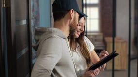 Lieferungs-, Post-, Leute- und Versandkonzept - glücklicher Mann, der Paketkästen zum Kundenhaus liefert Geben des Klemmbrettes f stock footage