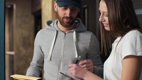 Lieferungs-, Post-, Leute- und Versandkonzept - glücklicher Mann, der Paketkästen zum Kundenhaus liefert Geben des Klemmbrettes f stock video