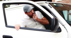Lieferungsfahrer, der auf Funksprechgerät spricht und in Packwagen kommt stock footage