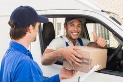 Lieferungsfahrer, der dem Kunden in seinem Packwagen Paket übergibt Stockbild