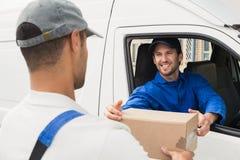 Lieferungsfahrer, der dem Kunden in seinem Packwagen Paket übergibt Lizenzfreie Stockfotos