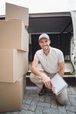 Lieferungsfahrer, der an der Kamera mit Stapel von Paketen lächelt Stockbilder
