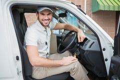Lieferungsfahrer, der an der Kamera in seinem Packwagen lächelt Stockfotografie