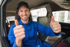 Lieferungsfahrer, der an der Kamera in seinem Packwagen lächelt Stockbild