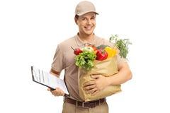 Lieferungskerl, der ein Klemmbrett und eine Einkaufstüte hält lizenzfreie stockfotos