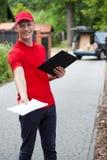 Lieferungskerl, der ein Paket gibt Lizenzfreie Stockbilder