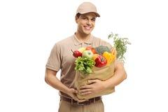 Lieferungskerl, der eine Tasche von Lebensmittelgeschäften hält lizenzfreie stockfotos