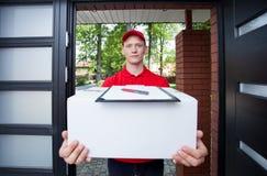 Lieferungskerl, der im Paket übergibt Lizenzfreies Stockbild