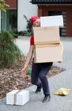 Lieferungskerl, der Pakete aufhebt Lizenzfreie Stockfotografie