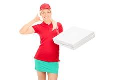 Lieferungsmädchen, das ein Rufzeichen macht und Pizza hält Lizenzfreies Stockfoto