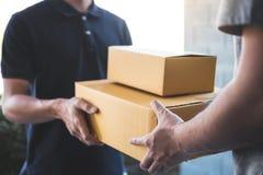 Lieferungspostmann, der der Empfänger, junges Inhaberannehmen Paketkasten des Pappschachtelpakets vom Postenversand, Haus gibt lizenzfreies stockbild