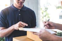 Lieferungspostmann, der Paketkasten zur Empfänger- und Unterzeichnungsform, unterzeichnende Ablieferungsbescheinigung des jungen  stockfoto