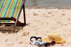 Liege steht auf dem Sand nahe dem Meer Sun-Strohhut, -Sandalen und -Sonnenbrille, die auf dem Sand liegen lizenzfreie stockbilder
