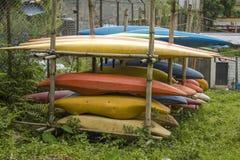 Liegen alte Kajaks und Kanus auf dem Freiluftgestell gelb-orangee blaue rote Plastikboote stockbild