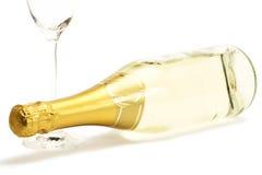 Liegenchampagnerflasche mit ein leeren Champagner glas Stockbild