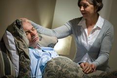 Liegender älterer Mann des Kranken und mitfühlende Frau Stockbilder