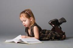 Liegendes und lesendes Mädchen. Stockbilder