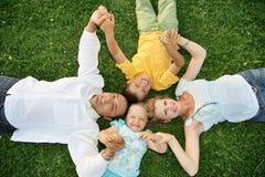 Liegenfamilie auf Gras Lizenzfreie Stockfotografie