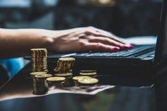 Liegt auf dem Tisch viele Goldmünzen, im Hintergrund Arbeiten einer Frau über einen Laptop lizenzfreie stockfotografie
