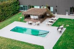 Lielupe hotell SPA & konferenser vid Semarah Simbassäng, utomhus- stång och vardagsrumtabeller royaltyfri bild