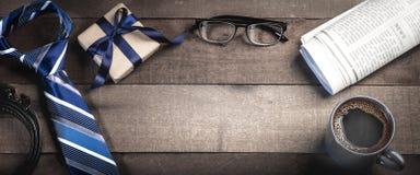Lien, ceinture, et boîte-cadeau avec des verres de lecture, des journaux, et le café photographie stock